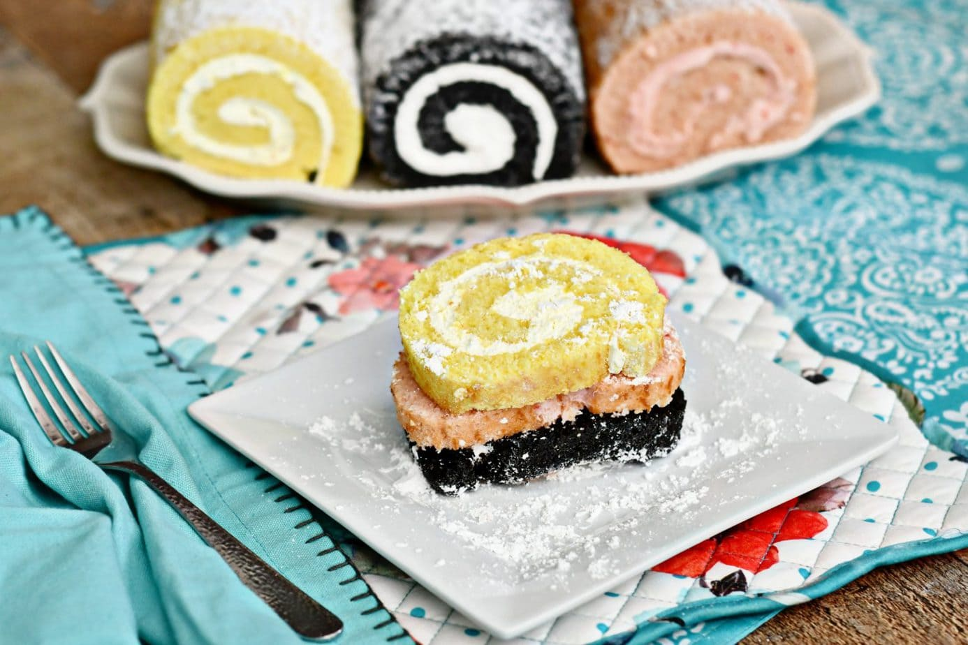 Brie Brie Blooms photo with Lemon, Chocolate, and Strawberry cake roll on multiple colored napkins and white plates