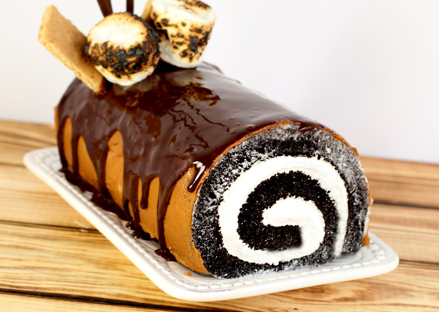 S'mores Cake Roll - cake roll with chocolate frosting, hot fudge, marshmallows, graham crackers, and chocolate sticks on white serving platter