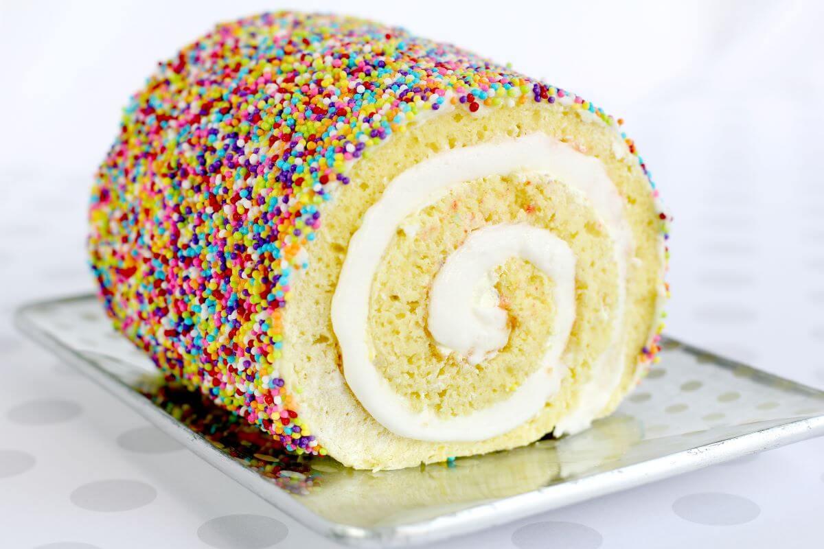 Sprinkle Cake Roll - lemon cake roll on metal serving tray, covered in sprinkles